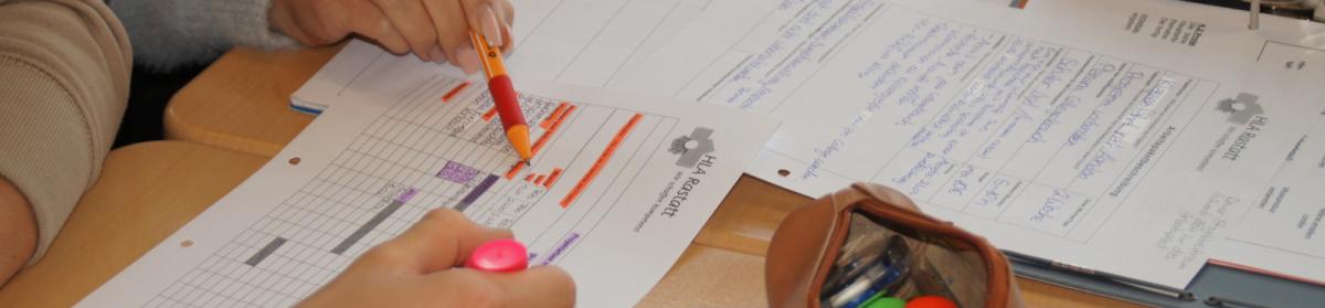 Aufnahme zweier Hände, Papiere werden gemeinsam bearbeitet, Textmarker und Mäppchen sind zu sehen