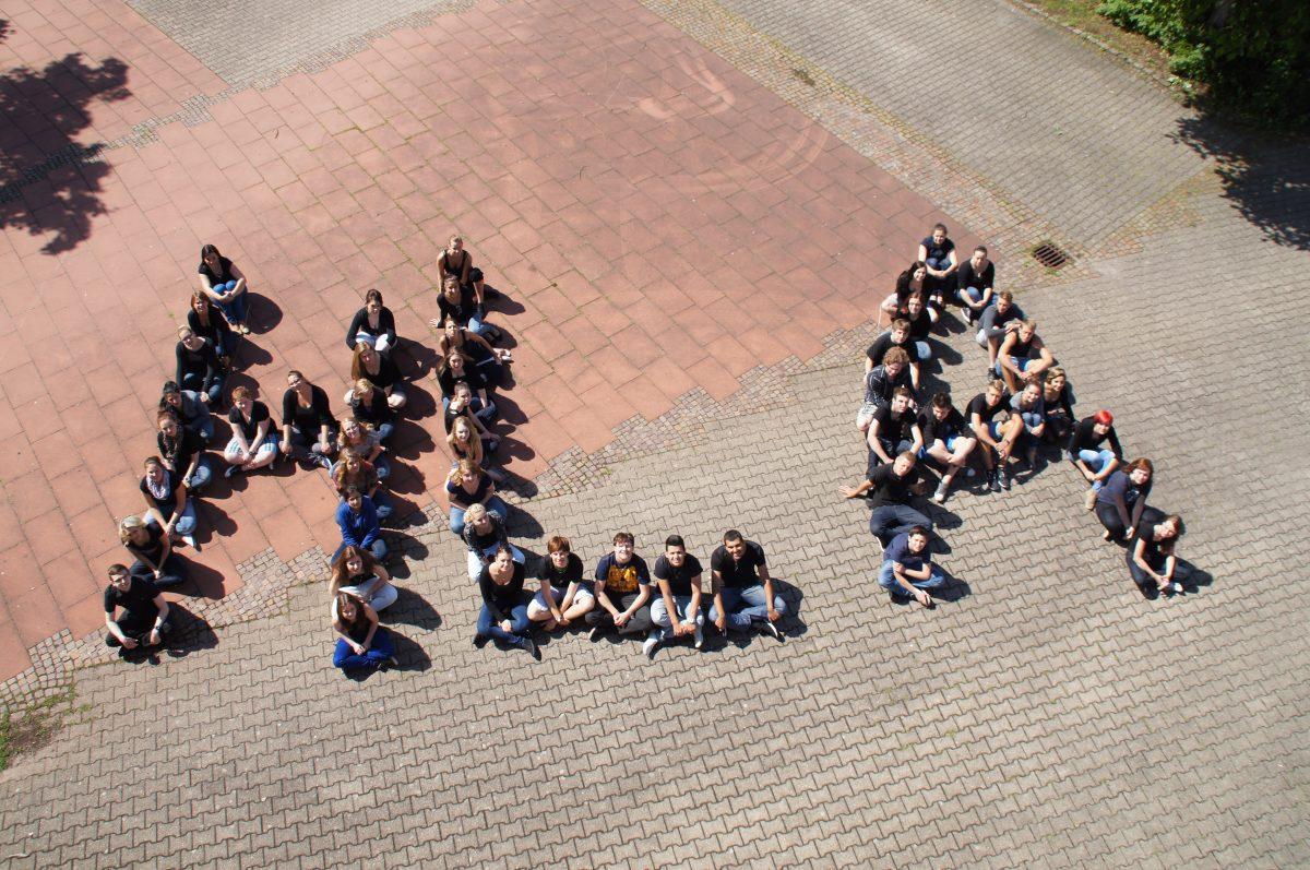 Schüler von oben fotografiert, sie bilden in ihrer Formation die Buchstaben HLA