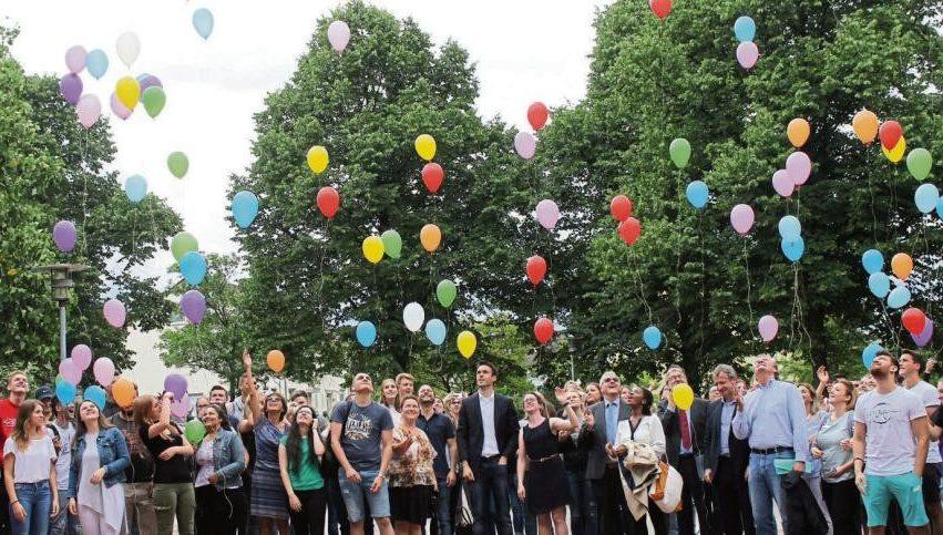 Eine Veranstaltungsgruppe lässt bunte Luftballons steigen